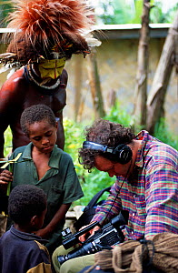 Huli people looking at camera equipment with Huw Cordey, producer for Jungles episode of BBC series Planet Earth, Tari Valley, Papua New Guinea, August 2004.  -  Tom Clarke