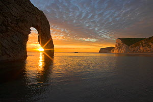 Sun setting through the arch at Durdle Door, Dorset, England, UK. Jurassic Coast World Heritage Site, March 2009  -  Peter Lewis