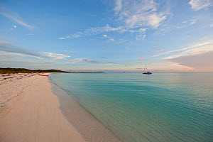 """People with tender pulled up on beach, exploring the Exumas. Their 30ft Tiki catamaran """"Abaco"""" is anchored offshore. Bahamas, Caribbean, June 2009. Model and property released. - Onne van der Wal"""
