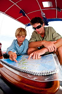 """Boy and young man reading a map aboard 30ft Tiki catamaran """"Abaco"""". Exumas, Bahamas, Caribbean. June 2009, Model and property released.  -  Onne van der Wal"""