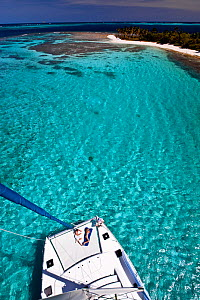 Couple sunbathing on the trampoline of a catamaran in the Grenadines, viewed from the masthead. Caribbean. February 2010.  -  Onne van der Wal