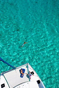 People sunbathing and swimming from a catamaran in the Grenadines, Caribbean. February 2010.  -  Onne van der Wal