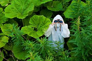 Boy in protective white suit and mask in the wilds surrounded by green vegetation, using binoculars, Scotland, UK, Model released - Niall Benvie