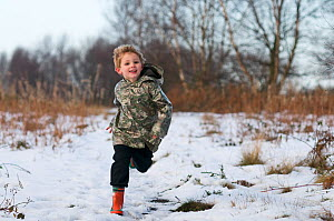 Young boy in red wellies running through snow in winter, Norfolk, England, UK. Model released  -  David Tipling