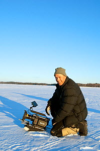 Cameraman Keith Brust filming with Red Camera, in snow covered landscape, Minnesota, USA, March 2008  -  Neil Lucas