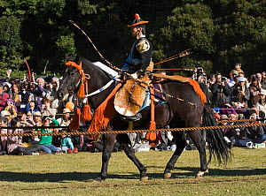A traditionally dressed samurai (warrior) from the Takeda School of Horseback Archery with bows and arrows parades on a horse, during a Yabusame (Japanese mounted archery), at Meiji Jingu Shrine, Toky... - Kristel Richard