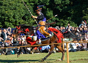 A traditionally dressed samurai (warrior) from the Takeda School of Horseback Archery with bows and arrows galloping on a horse between targets, during a Yabusame (Japanese mounted archery), at Meiji...  -  Kristel Richard