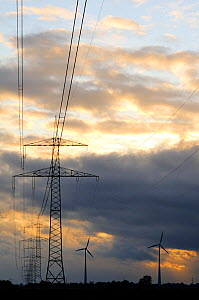 Electricity cables, pylons and wind turbines at sunset. Near Diepholz, Lower Saxony, Germany. - Nick Upton