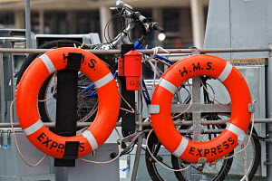"""Lifebelts of """"HMS Express"""" with bicycles chained to the railings behind them. Canning dock, Liverpool, UK, July 2010. Editorial only. - Norma Brazendale"""