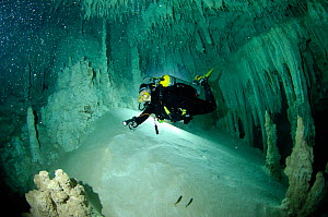 Diver exploring a freshwater Limestone sinkhole / Cenote called 'The Pit' - a traverse to 'The Blue Abyss' with stalactites and stalagmites, Tulum, Quintana Roo, Mexico, September 2008. Model released - Robert Smith