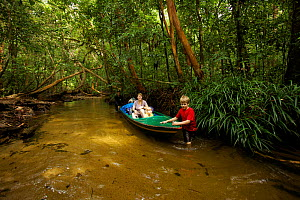 Mother and two young children (all model released)traveling by boat downstream from the research camp in Gunung Palung NP Borneo. July 2007  -  Tim Laman