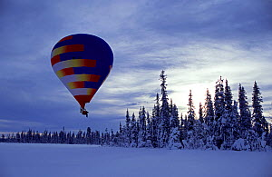 Cameraman in a 'cinebulle' (a hot air balloon adapted for filming) to film the landscape without disturbing the snow, Lapland, Finland for BBC series Planet Earth.  -  Tom Clarke