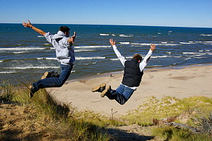 Two boys leaping off sand dunes beside Lake Michigan, Holland, Michigan, USA, model released, October 2004  -  Tim Laman