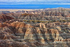 View of Badlands National Park, with shadows cast between mountain peaks, and sediment layers visible, South Dakota, USA. September 2009. - Ingo Arndt