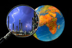 Lightning during thunderstorm above petrochemical industry seen through magnifying glass held against illuminated globe of the earth Digital composite  -  Philippe Clement