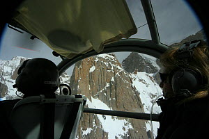 Rear view of pilot and director Vanessa Berlowitz  filming in the Karakoram Mountains, Himalayas, Pakistan. From Pakistani military helicopter for BBC series Planet Earth, April 2005 - Jeff Wilson
