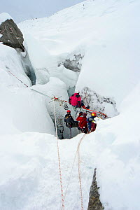 Film crew lowering camera into crevasse in Gorner glacier, near Zermatt in the Swiss Alps, Switzerland, for BBC Planet Earth series, Mountains episode, 2006  -  Jeff Wilson