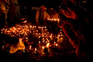 People lighting candles inside Mosque at night, Lahore, Pakistan, 2006  -  Jeff Wilson