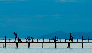 People with bicycles on jetty, Sipidan Island, Borneo, January 2006. - Charlie Dailey