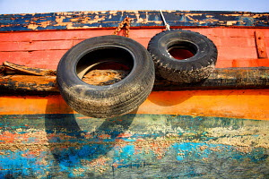 Tyres used as fenders on colourful wooden hull, Palma boat yard, Mallorca, Spain, March 2008. - Charlie Dailey