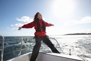 Young woman enjoying breeze on board yacht, Kerteminde, Denmark, September 2010. Model and property released. - Gary John Norman