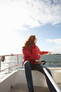 Young woman at the helm on board yacht, Kerteminde, Denmark, September 2010. Model and property released. - Gary John Norman