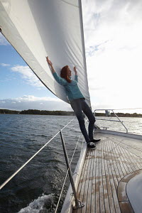 Young woman relaxing on foredecks of yacht, Kerteminde, Denmark, September 2010. Model and property released. - Gary John Norman