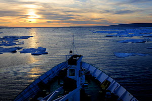 View across the bow of the Lyubov Orlova ship,  moving through pack ice  at dawn, off the coast of Devon Island. Nunavut, Canada,  August 2010  -  Eric Baccega