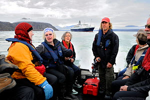Tourists and guide in a Zodiac rib, with cruise ship in background, Nunavut, Canada, August 2010  -  Eric Baccega