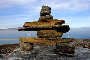 A traditional Inukshuk sculpture in figurative form, on the coast of Sunshine Fjord, with a cruise ship behind, Nunavut, Canada, August 2010  -  Eric Baccega