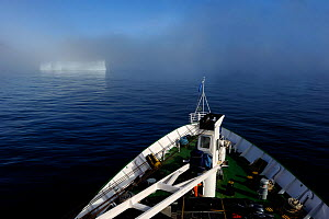 View from deck of a cruise ship cruising along Baffin Island with an iceberg emerging out ot the mist, Nunavut, Canada, August 2010 - Eric Baccega