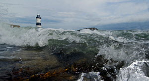 A low angle view of Penmon lighthouse with waves crashing towards the camera, Anglesey, Wales, October 2009. - Graham Eaton