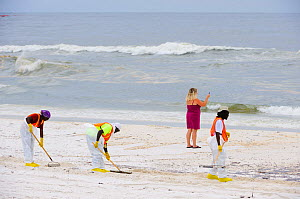 Beach cleaners, and a woman taking a cell phone photo of the oil contamination, resulting from the BP Deepwater Horizon oil leak in the Gulf of Mexico, Orange Beach, Baldwin County, Alabama, USA, June... - Gerrit Vyn