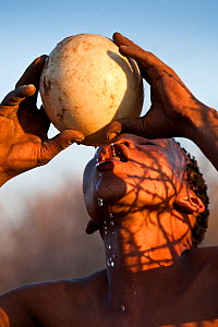 'Xamse', a young Kalahari bushman, drinking water from an ostrich's egg in the dry season, egg was buried underground during the rainy season. Kalahari Desert, Botswana, August 2008 - Christophe Courteau