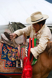A Khampa warrior saddles his Tibetan horse, during the horse festival, near Huangyan, in the Garze Tibetan Autonomous Prefecture in the Sichuan Province, China, June 2010 - Kristel Richard