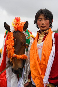 The winner of the endurance race and his Tibetan horse are covered with scarves, during the horse festival, near Huangyan, in the Garze Tibetan Autonomous Prefecture in the Sichuan Province, China, Ju... - Kristel Richard