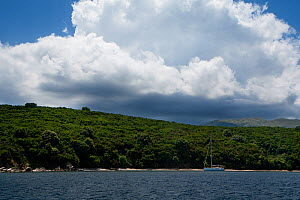 Sailing yacht anchored off a deserted beach, north-east Corfu, Greece, June 2010. - Toby Roxburgh