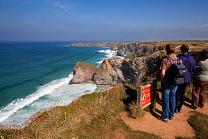 Group of walkers standing on top of the cliffs looking out at the view, Bedruthan Steps, Cornwall Area of Outstanding Natural Beauty (AONB), England, August 2010.  -  Toby Roxburgh
