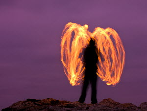 Man fire spinning (Fire Poi) on Cornish clifftops, Godrevy, Cornwall, England. October 2009 - Adam Burton