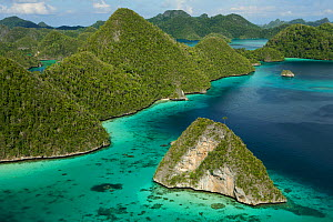 Aerial view of a boat making its way through the Wayag Islands, an uninhabited group of uplifted limestone (karst) islands, NW of Waigeo Island. West Papua, Indonesia, April 2007  -  Tim Laman