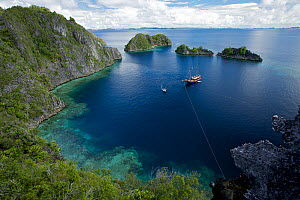 The ship Shakti, chartered for a GEO Expedition, is tied off in small bay surrounded by limestone cliffs and islets. Misool Island vicinity. Near smaller island of Fiabacet. West Papua, Indonesia, Apr... - Tim Laman