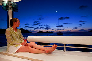 "Woman relaxing on board Privilege 745 catamaran ""Matau"" while cruising in the Grenadines, Caribbean, January 2010. Model and Property released.  -  Billy Black"