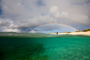 Figure beneath rainbow on Sandy Island, near Carriacou Island, the Grenadines, Caribbean, January 2010.  -  Billy Black