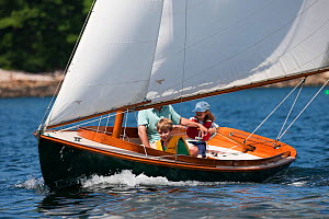 Father teaching children to sail in wooden boat.   Rockport, Maine, USA, August 2010. Model released.  -  Billy Black