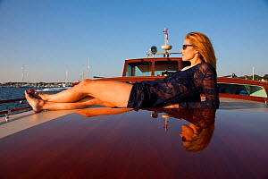 "Woman relaxing on board luxury motorboat ""Aphrodite"". Newport, Rhode Island, USA, July 2010. Model and Property released.  -  Billy Black"