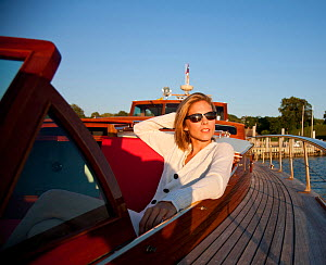 """Woman relaxing in cockpit on board luxury motorboat """"Aphrodite"""". Newport, Rhode Island, USA, July 2010. Model and Property released.  -  Billy Black"""