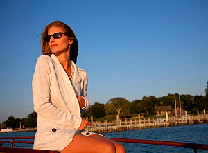 """Woman relaxing on board luxury motorboat """"Aphrodite"""". Newport, Rhode Island, USA, July 2010. Model and Property released.  -  Billy Black"""