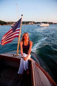 "Woman relaxing on stern of luxury motorboat ""Aphrodite"". Newport, Rhode Island, USA, July 2010. Model and Property released.  -  Billy Black"