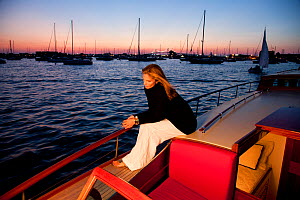 """Woman relaxing on stern of luxury motorboat """"Aphrodite"""" in the evening. Newport, Rhode Island, USA, July 2010. Model and Property released.  -  Billy Black"""