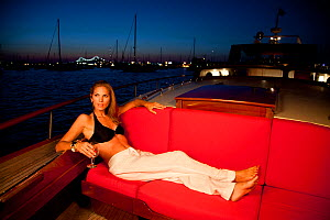 """Woman enjoying evening glass of wine on board luxury motorboat """"Aphrodite"""". Newport, Rhode Island, USA, July 2010. Model and Property released.  -  Billy Black"""